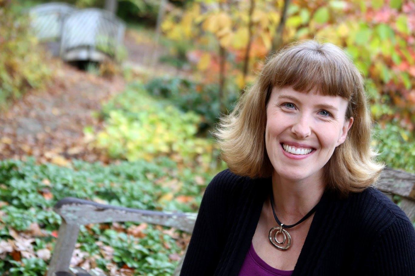Bethesda Doula Jenny Corbett smiling in front of fall leaves