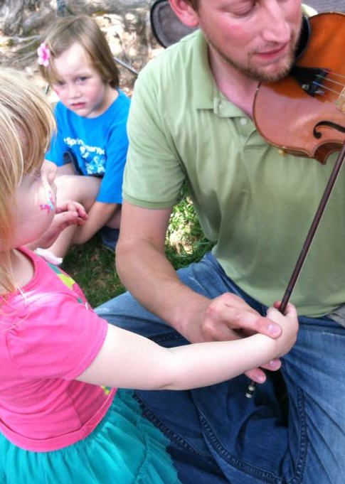 Man shows child how to play the fiddle fun things to do with kids in DC