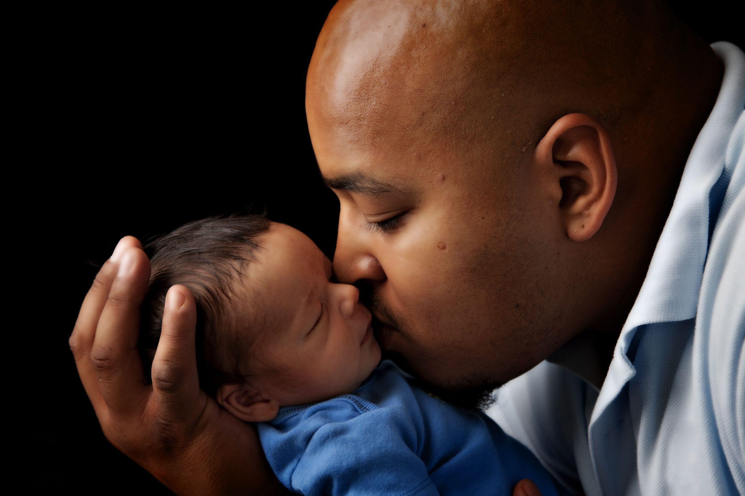 African America dad kissing his newborn after getting birth support from Silver Spring Doula during covid-19